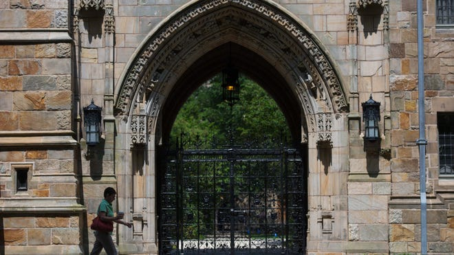 A pedestrian walks past Harkness Gate on the Yale University campus in New Haven, Conn., on June 12, 2015.