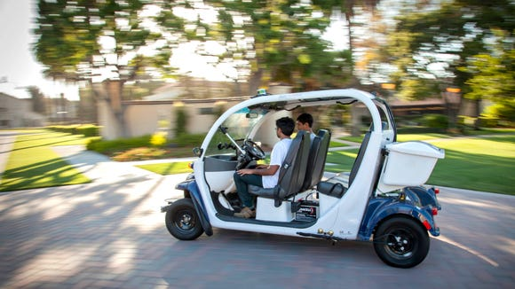 (From left to right) Srinivas Reddy, the Co-founder and Product Lead, and Jit Ray Chowdhury, Co-founder and CTO, for Auro Robotics demonstrate their company's driverless shuttle. (Photo credit: Joanne H. Lee/Santa Clara University)