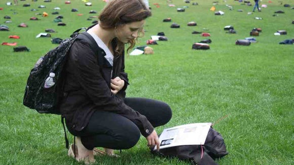 Sarah Moss, co-president of NU Active Minds, reads a personal story at the Send Silence Packing display held at Northwestern University. (Medha Imam)
