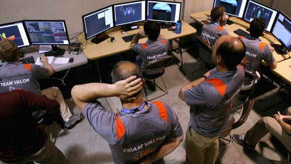 Members of Virginia Tech's Team Valor sit at the computers where they wirelessly control their semi-autonomous ESCHER (Electromechanical Series Compliant Humanoid for Emergency Response) robot during the second day of the Defense Advanced Research Projects Agency (DARPA) Robotics Challenge at the Fairplex June 6, 2015 in Pomona, California.  (Photo by Chip Somodevilla/Getty Images)