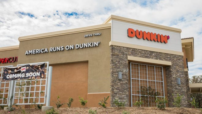 """A Dunkin' outlet with an """"America Runs on Dunkin'"""" sign."""