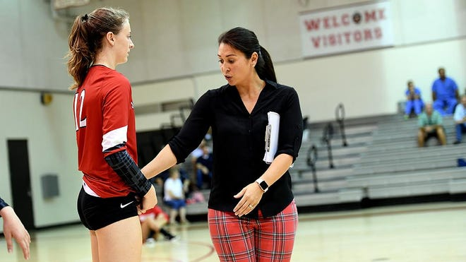 St. Andrews volleyball coach Dawn Jones talks to a player on the sidelines during a match.