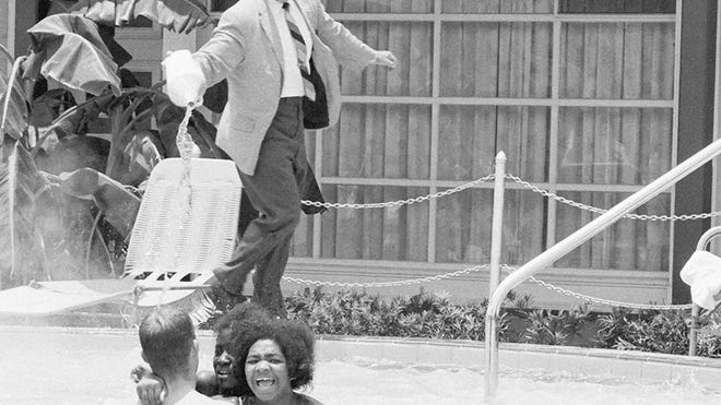 James Brock, manager of the former Monson Motor Lodge in St. Augustine, pours acid into the hotel's segregated pool after a group of civil rights activists entered to swim on June 18, 1964.