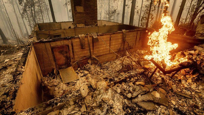 Flames burn at a home leveled by the Creek Fire along Highway 168 on Tuesday, Sept. 8, 2020, in Fresno County, Calif.