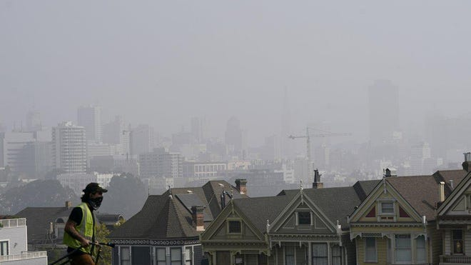 """A worker cleans grass at Alamo Square Park as smoke from wildfires and fog obscures the skyline above the """"Painted Ladies,"""" a row of historical Victorian homes, in San Francisco, Monday, Sept. 14, 2020."""