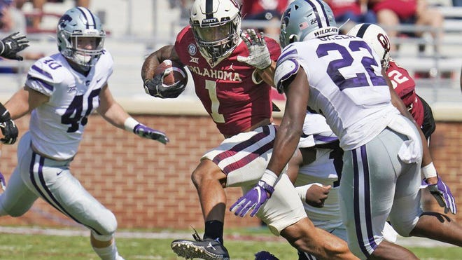 Oklahoma running back Seth McGowan, center, carries between Kansas State defensive end Spencer Trussell, left, and linebacker Daniel Green in the second half on Saturday, Sept. 26, 2020, in Norman.