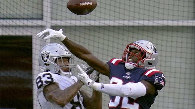 New England defensive back Devin McCourty breaks up a pass intended for Las Vegas tight end Darren Waller during Sunday's game.