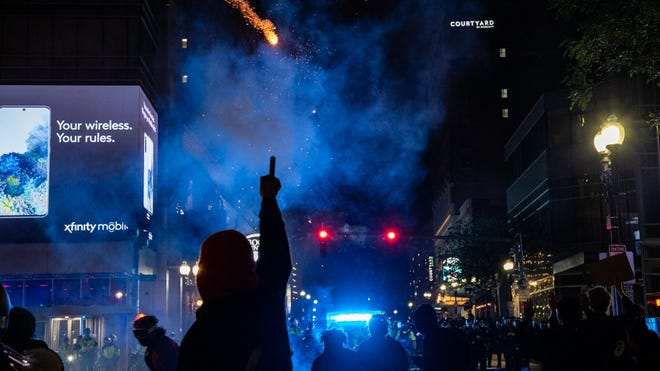 A protestor shot off a firework toward Boston police at the intersection of Tremont and Stuart streets.