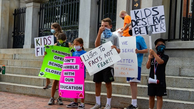 A group of children stood outside the State House Wednesday holding signs as parents rallied for an in-person education in the fall.