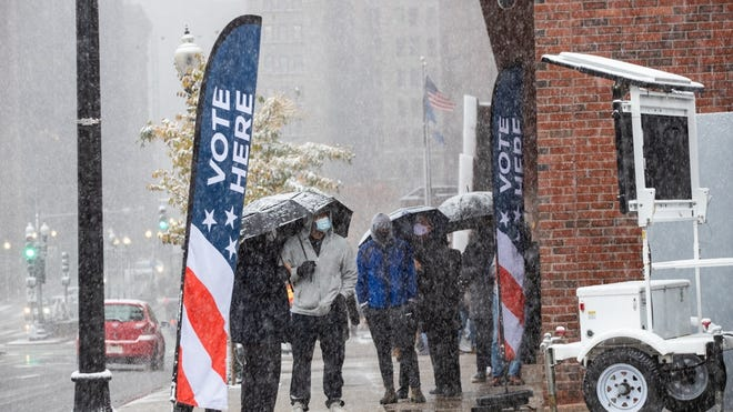 Boston residents stood in line Friday morning on the last day of early voting at City Hall as snow swirled and whirled around them.