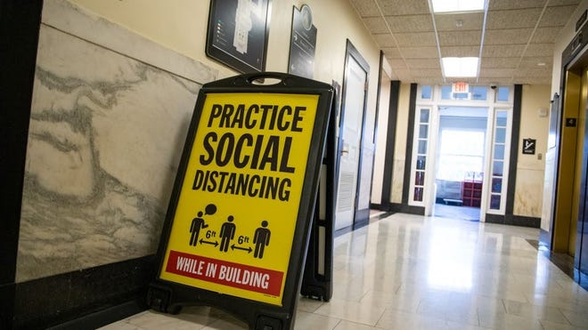Signs encouraging social distancing were a new addition Monday, June 29 in the otherwise nearly-empty State House corridors.