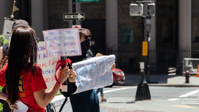 """A protester on the sidewalk in front of One Beacon St., where UMass President Marty Meehan's offices are located, held a sign Wednesday reading """"This is the biggest sign I can afford (I teach @ UMB)."""""""