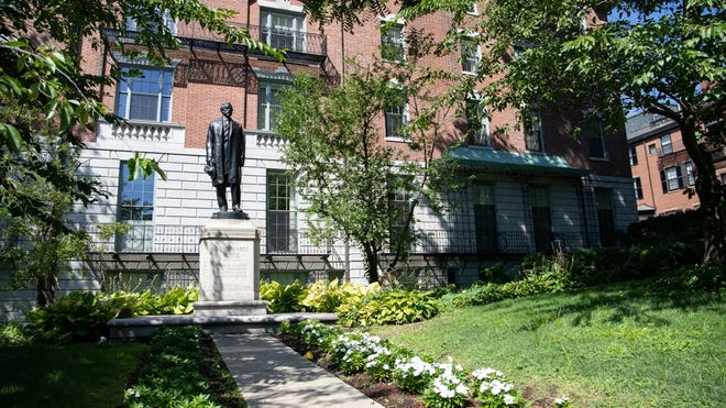 A statue of former U.S. Senate Majority Leader Henry Cabot Lodge stands on the State House west lawn, the site of his now-demolished boyhood home. Rising behind Lodge is 25 Beacon St., former headquarters of the Unitarian Universalist Association.