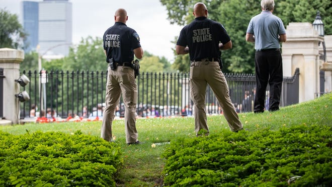 State Police troopers stood on the State House front lawn Monday while lawmakers on the sidewalk below unveiled the Senate's sweeping package of police reforms.