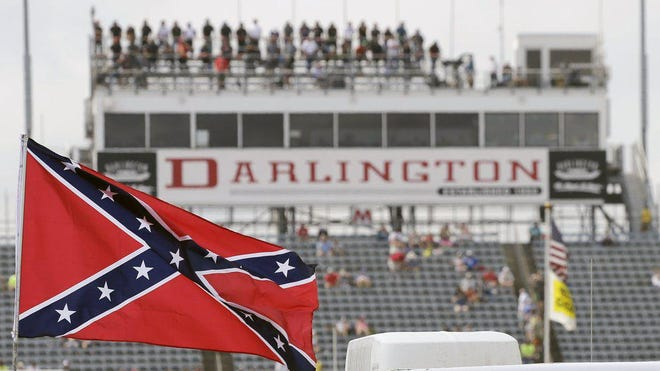 In this Sept. 5, 2015, file photo, a Confederate flag flies in the infield before a NASCAR Xfinity auto race at Darlington Raceway in Darlington, S.C. Bubba Wallace, the only African-American driver in the top tier of NASCAR, called for a ban on the Confederate flag in the sport that is deeply rooted in the South.