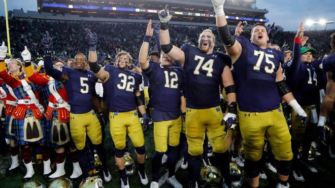 In this Nov. 2, 2019, file photo, members of the Notre Dame football team sing after an NCAA college football game against Virginia Tech in South Bend, Ind.
