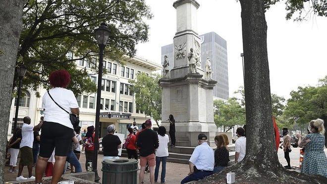 People hold a rally at the Confederate monument in Augusta, Ga., Saturday morning, August 8, 2020.