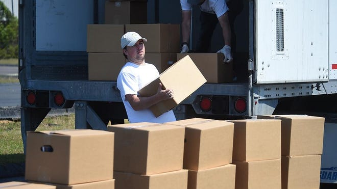 Volunteers distribute food boxes from Golden Harvest at New Passion Church in Augusta, Ga., Monday afternoon April 6, 2020. A total of 2,000 boxes of nonperishable food items are available to be distributed to families in need. Distribution continues on Wednesday and Friday.