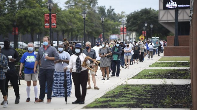Voters line up outside the Bell Auditorium for the first day of advance voting  in Augusta, Ga., Monday morning October 12, 2020