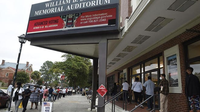 FILE- Voters line up outside the Bell Auditorium for the first day of advance voting  in Augusta, Ga., Monday morning October 12, 2020
