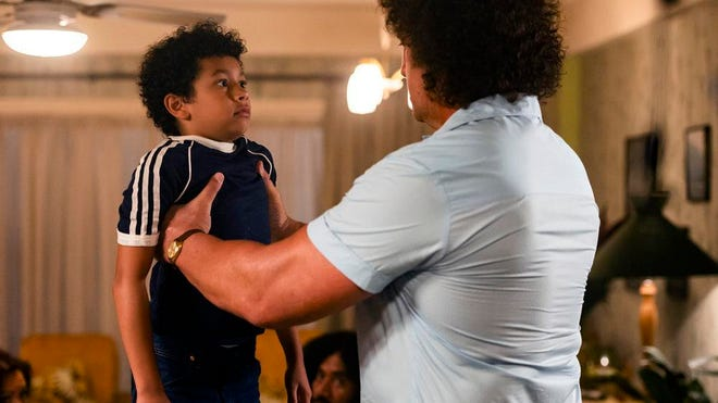 """Adrian Groulx as Dwayne Johnson, left, and Matthew Willig as Andre the Giant in a scene from """"Young Rock,"""" which debuts Tuesday on NBC."""