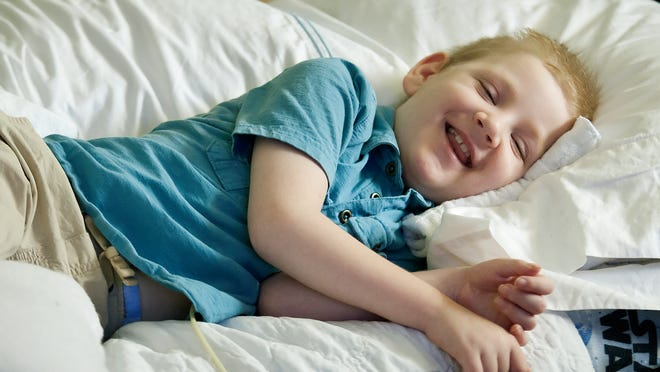 """Christian Hannett, 8, laughs while watching the movie """"Frozen"""" on Sunday in his North Naples Home. Christian suffers from a genetic disorder called metachromatic leukodystrophy."""