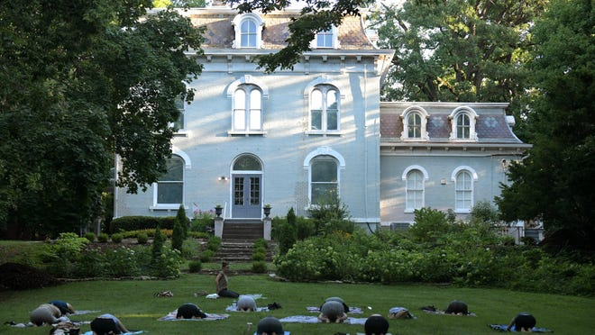 Students in Soulside Healing Arts sunrise yoga class practice outside the PettenGill-Morron House on Peoria's historic Moss Avenue on Thursday morning.