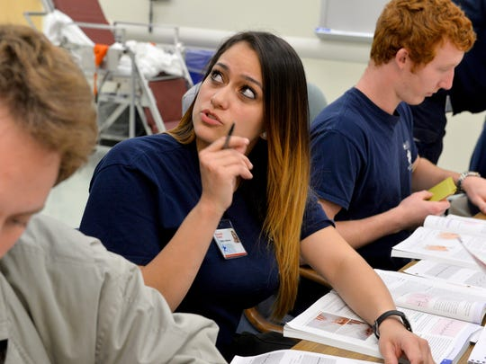 Lansing Community College paramedic program student Sierra Medrano talks with instructor Peter Haueter as students work in a lab  at the school. Medrano recently put her training to good use by performing CPR on a car accident victim.