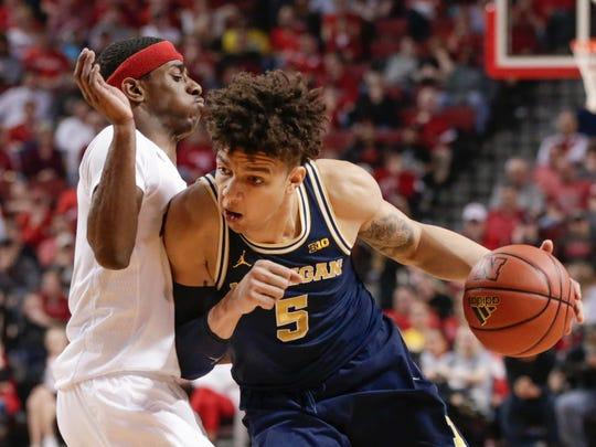 Michigan's D.J. Wilson (5) tries to get around Nebraska's Glynn Watson Jr., left.