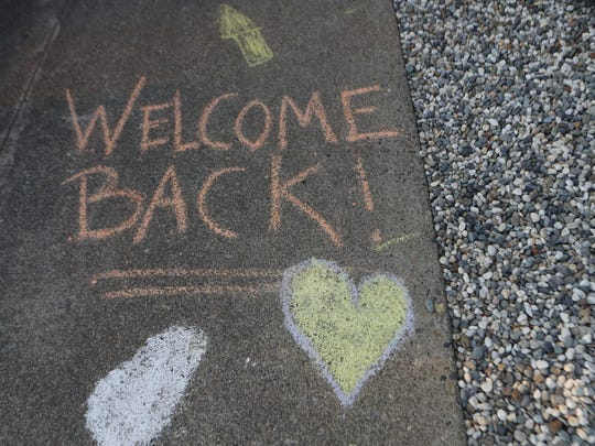 Chalk messages on the sidewalk welcome students back to Manzanita Elementary School.