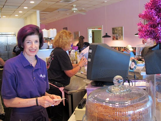 Jeri Holecek, left, waits on customers in January 2017 at her purple-hued LuLu B's Grill in Marketplace at Pelican Bay in North Naples. Holecek plans to open LuLu B's Diner this fall in Green Tree Center.
