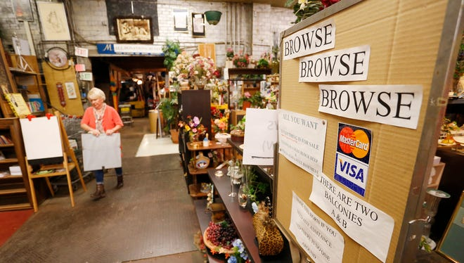 Connie Joy, background left, carries a picture to a showroom Tuesday, April 3, 2018, at Chestnut Street Mercantile, 231 Chestnut Street in Lafayette. Chestnut Street Mercantile has an eclectic collection of items, from golf clubs, to furniture, to bicycles and more, all for sale. Proceeds benefit the YWCA and it's programs.
