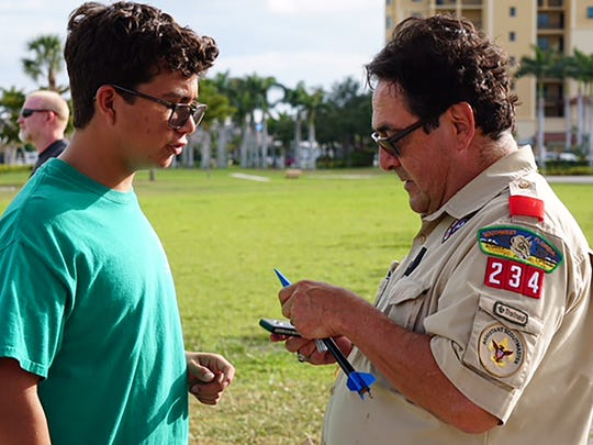 Boy Scout Joey Puell and his father Jose Puell inspecting a rocket.