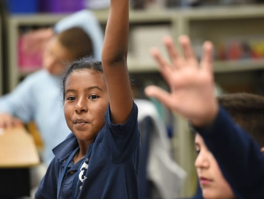 Bsrat Kidane raises her hand to answer a question at