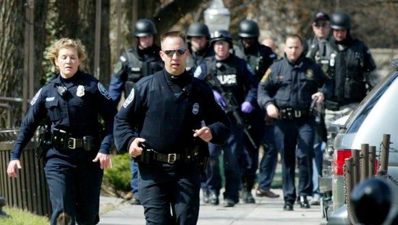 Blacksburg police officers run from Norris Hall on