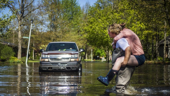 Ryan Stadelmaier, 16, gives a piggyback ride to his sister Rachel Stadelmaier, 27, as they cross a road while helping residents tend to their flooded homes on May 20 in Midland, Mich.