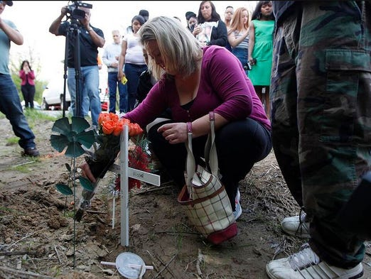 Brandi Stewart, mother of Samantha Ramsey, moves to place a cross and flowers on the spot where her daughter was shot by a Boone County Deputy after a field party on River Road in Hebron.