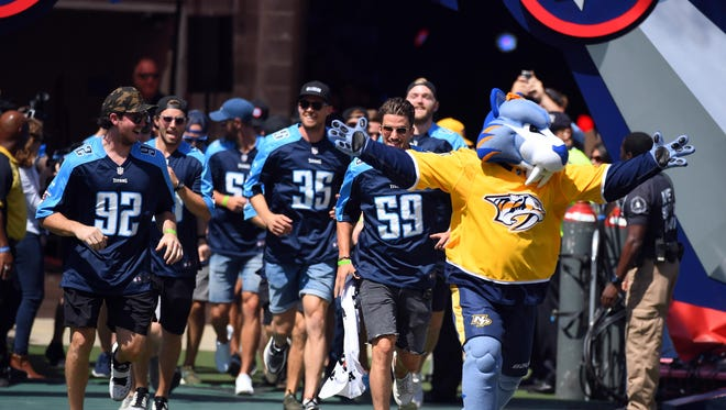 Nashville Predators mascot Gnash leads the Predators players onto the field before the Tennessee Titans game against the Oakland Raiders at Nissan Stadium. Mandatory Credit: Christopher Hanewinckel-USA TODAY Sports