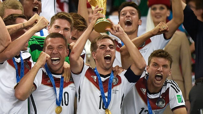 Germany's Philipp Lahm raises the trophy after the 2014 World Cup final soccer match between Germany and Argentina in Rio de Janeiro, Brazil.