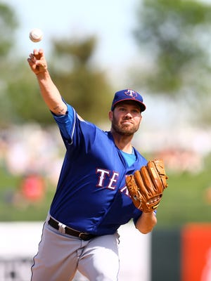Texas Rangers pitcher Colby Lewis throws against the Kansas City Royals during a 2016 spring training game.