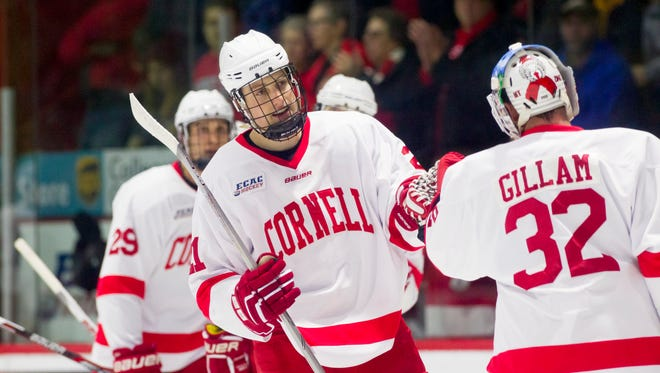 Cornell's Dwyer Tschantz, center, celebrates a goal with goalie Mitch Gillam during the 2015-16 season.