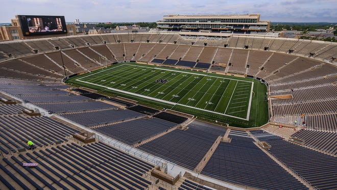 Recently renovated Notre Dame Stadium features a 96-by-54-feet high definition video board above the south end zone, at top left, and new seating around the top tier, at bottom left, seen during a media tour at the University of Notre Dame campus, South Bend, Ind., Friday, August 11, 2017. Former wooden benches that were removed are decoratively repurposed throughout the stadium's interior.