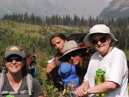 Amy Lewin, Kqyn Kuka-Macguire, Khi Soldano and Vicki Boyd stop for a break from the climbing trail and their heavy packs.