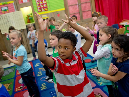 Kindergarten student Tayveon Roberston, 5, dances along