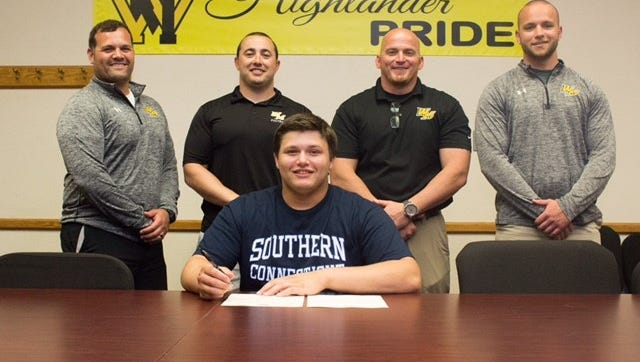 West Milford senior football player Eric Lindstrom, center, committed to Southern Connecticut State University last week with (L-R) assistant coach Gary Stoll, head coach Don Dougherty, assistant coach Steve Maslanek and assistant coach Eric Kagdis by his side.