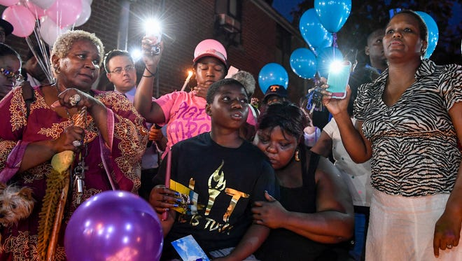 Deberianah Begley's brother Danquan and mother Tika Begley are surrounded by friends and family during a candlelight vigil at the James Cayce Public Housing Development in Nashville, Tenn., Monday, Oct. 9, 2017.