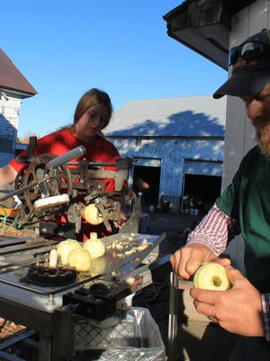 Bailey McNamara and her father, Chris, prepare apples at Clearview Farm for baking. The farm's apples, cider donuts and baked apples are among the items customers take away each fall.