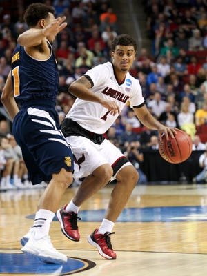 U of L's Quentin Snider, #2, drives against UC Irvine's Alex Young, #1, at the KeyArena in Seattle during the second round of the NCAA tournament.