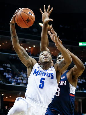 University of Memphis guard Markel Crawford (front) drives for a layup against University of Connecticut defender Steven Enoch (back) during first half action at the FedExForum.