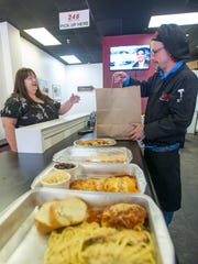 Owner Ken Hudson, right, bags a meal for new customer